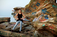 Senior standing on rocks with graffiti