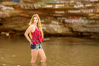 senior portrait in water by rock formation